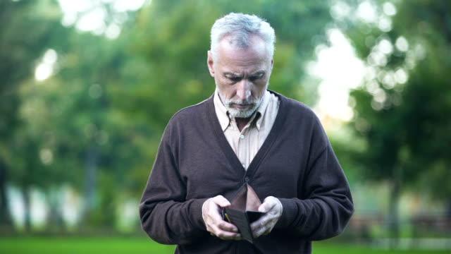 Sad-pensioner-holding-empty-wallet-retirement-poverty-financial-crisis-credit
