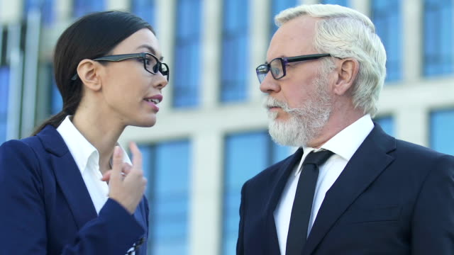 Old-businessman-not-listening-to-young-female-employee-gender-discrimination