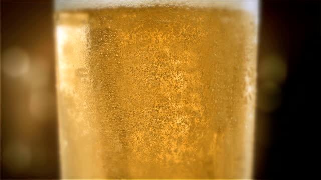 Close-up-Zeitlupen-Kaltlicht-Bier-in-einem-Glas-mit-Wasser-tropft-auf-bar-Hintergrund-Craft-Bier-hautnah