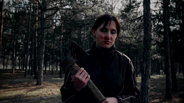 Scary-woman-zombie-with-axe-goes-and-does-spit-blood-after-eating-of-victim-in-woods