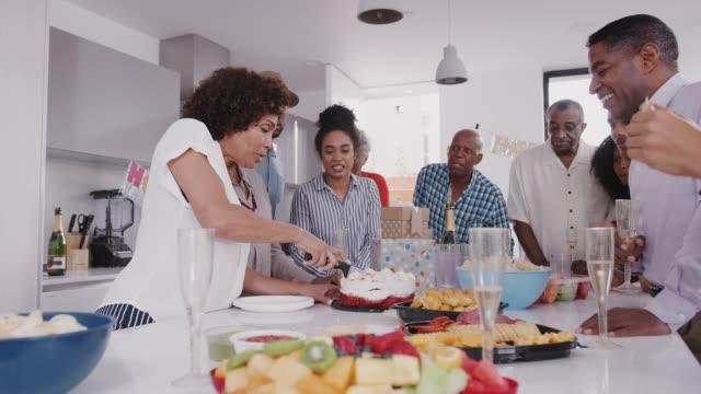 Drei-Generation-schwarzer-Familie-stehen-um-einen-Tisch-während-Mutter-bei-Geburtstagsfeier-den-Kuchen-schneidet