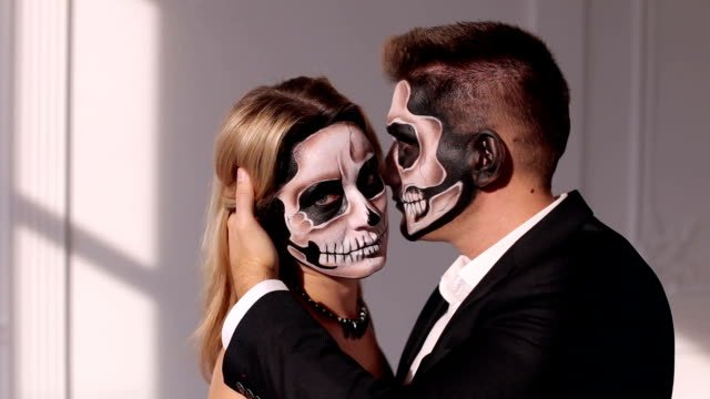 Close-up-view-of-couple-of-painted-halloween-holy-characters-woman-and-man-