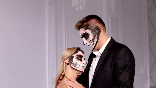 Close-up-of-a-creepy-girl-with-makeup-for-Halloween-a-man-holding-her-neck-