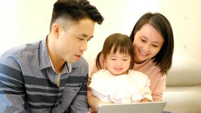 Asiatische-Eltern-Vater-und-Mutter-und-Tochter-spielen-mit-digitalen-Tablet-auf-dem-Sofa