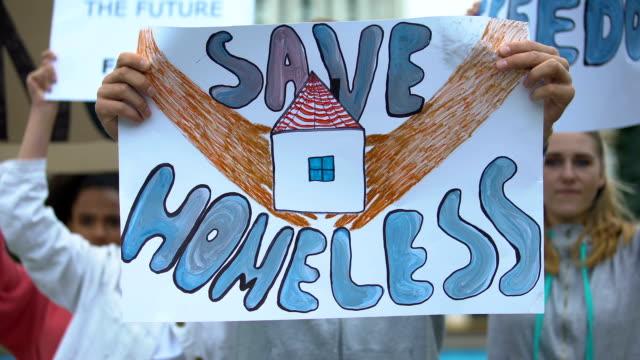 Activistas-con-cartel-de-Save-homeless-cantando-para-apoyar-a-los-migrantes-derechos-de-los-refugiados