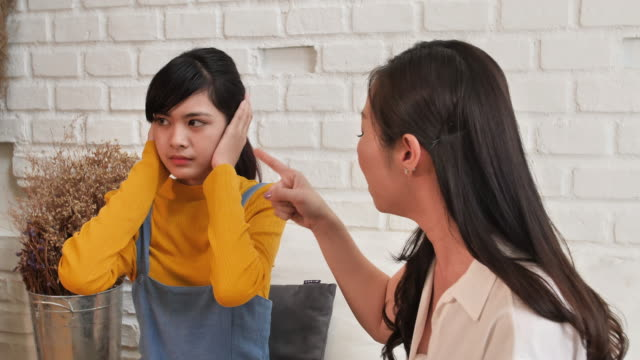 Asian-family-Teenage-daughte-closed-his-ears-with-his-hands-while-her-mother-yells-at-her-at-home-Family-crisis-conflict-and-relationships-problems-concept