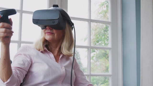 Mature-Disabled-Woman-In-Wheelchair-At-Home-Using-Virtual-Reality-Headset-Gaming-Holding-Controllers
