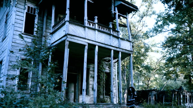Halloween-A-young-woman-with-make-up-of-skeleton-going-along-a-wooden-house-4K