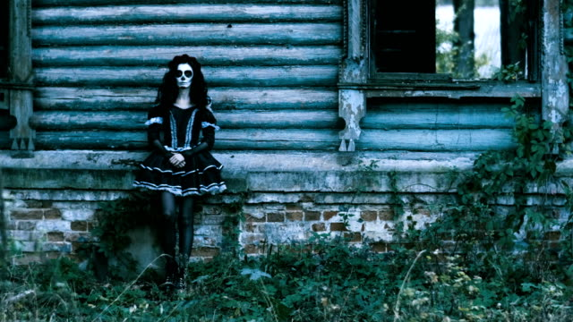 The-woman-with-halloween-make-up-in-black-clothes-standing-in-front-of-house-4K