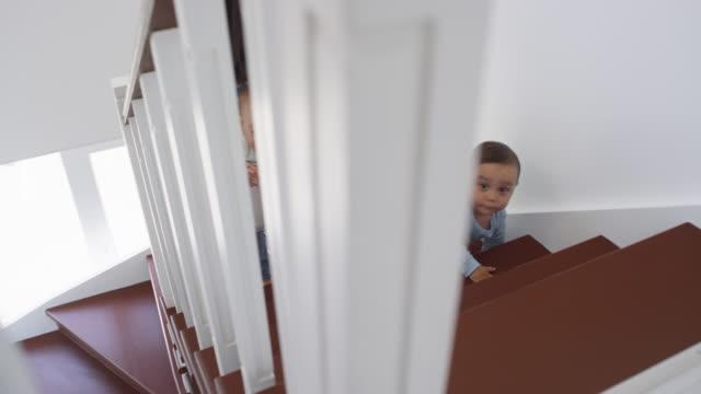 Los-trillizos-asiáticos-para-niños-pequeños-se-arrastran-por-la-escalera-y-la-mamá-ayuda
