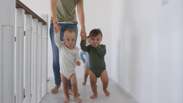 Mujer-irreconocible-liderando-trillizos-asiáticos-de-bebé-a-mano-en-casa