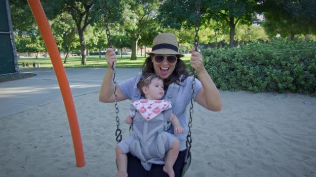 Frau-schwingt-auf-einer-Schaukel-mit-Baby-auf-Trage-auf-Spielplatz