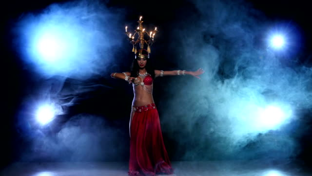 Attractive-belly-dancer-continue-dancing-with-candles-on-her-head-black-smoke
