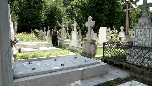 Funeral-gothic-girl-walking-beside-tombstones-in-ancient-graveyard-contemplating-death-and-solitude