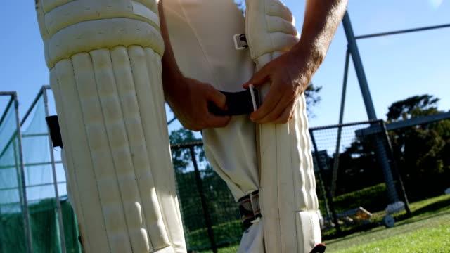 Cricketspieler-binden-seine-Watte-Pads-während-einer-Übung
