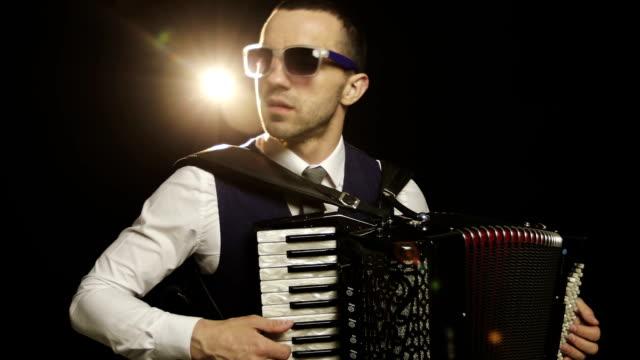 Un-músico-de-moda-en-una-camisa-blanca-toca-el-acordeón-en-el-estudio-sobre-un-fondo-negro-