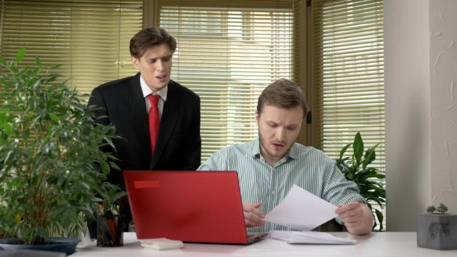 A-young-subordinate-employee-brought-the-boss-a-report-a-document-Makes-funny-faces-while-the-boss-does-not-see-behind-his-back-Work-in-the-office-60-fps