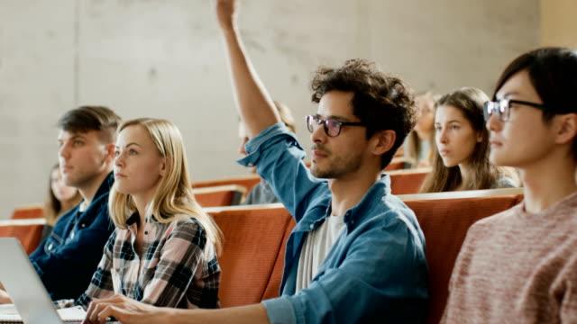 Gut-aussehend-Hispanic-Student-nutzt-Laptop-beim-Hören-eines-Vortrags-an-der-Universität-er-wirft-Hand-und-fragt-Dozent-einer-Frage-Multi-ethnischen-Gruppe-von-modernen-hellen-Studenten-
