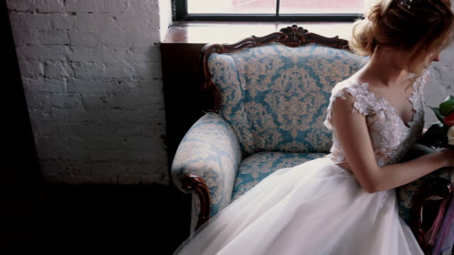 young-bride-holding-a-bouquet-sitting-in-a-chair