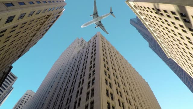 BOTTOM-UP:-Large-commercial-airplane-flies-low-and-close-to-tall-skyscrapers.