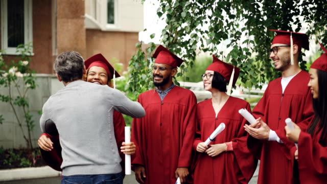 Freundlichen-stolz-Professor-ist-froh-dass-afrikanische-amerikanische-Studentin-umarmt-und-dann-ihre-Hand-schütteln-wünscht-viel-Glück-zu-Mulninational-Gruppe-von-Studenten-