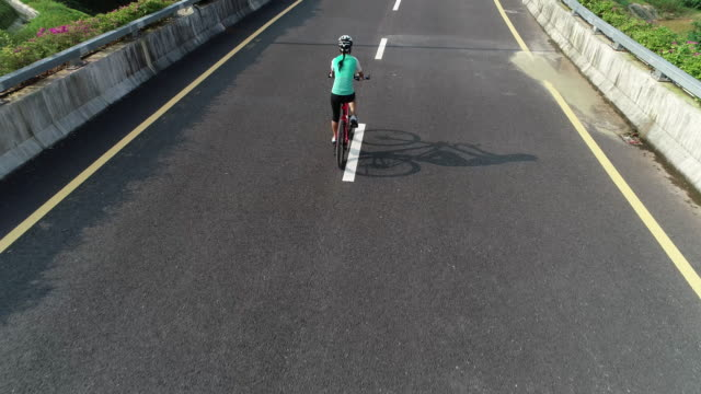 Aerial-view-of-experienced-woman-hands-free-cycling-riding-bike-on-highway-road