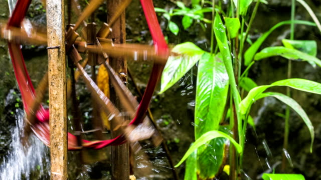 Bamboo-water-wheel-used-for-irrigation-brings-water-from-stream-to-plantation-Close-up-of-bamboo-wheel-delivering-water-Asia