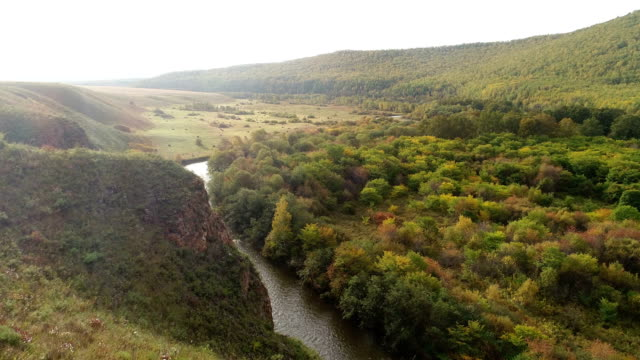 Aerial-Drone-Footage-View:-Flight-over-autumn-mountains-and-small-river-with-forests-in-sunrise-soft-light-Majestic-landscape-