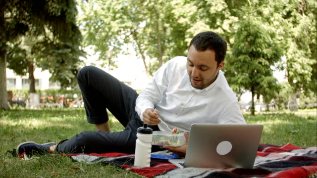 Attractive-man-at-lunch-time-in-the-park-say-something-on-the-camera