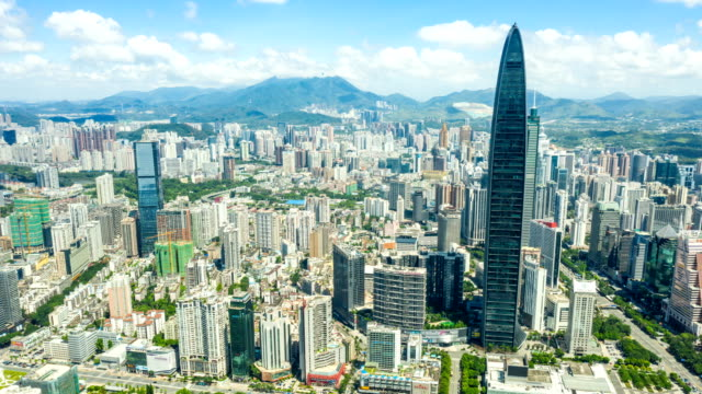 Aerial-hyper-lapse-of-Shenzhen-cityscape-under-cloudy-sky-