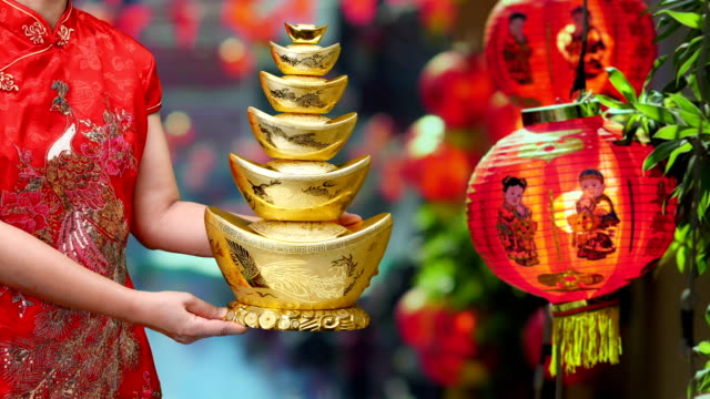Woman-holding-Chinese-new-year-gold-ingots-(qian)-in-chinatown