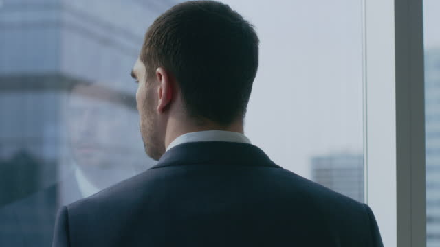 Primer-tiro-del-empresario-pensativo-en-un-juego-de-pie-en-su-oficina-y-contemplando-próximo-gran-negocio-mirando-por-la-ventana-Ventana-panorámica-grande-distrito-de-negocios-de-la-ciudad-