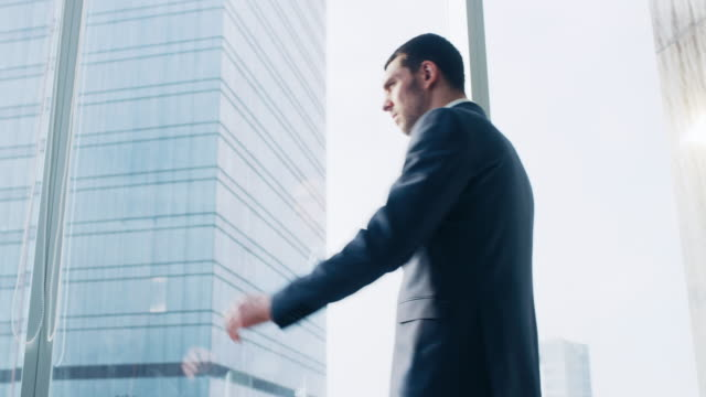 Low-Angle-Following-Shot-of-the-Confident-Businessman-in-a-Suit-Walking-Through-His-Office-and-Looking-out-of-the-Window-Thoughtfully-Stylish-Modern-Business-Office-with-Big-City-View-