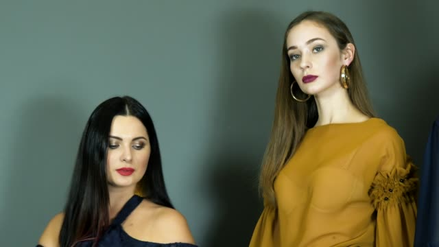 models-during-fashion-week-close-up-pose-on-background-wall-at-photo-shoot