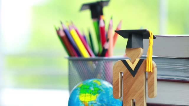 Education-knowledge-learning-study-abroad-international-Ideas-People-Sign-wood-with-Graduation-celebrating-cap-on-open-textbook-America-global-map-show-alternative-studying-Back-to-School-Concept