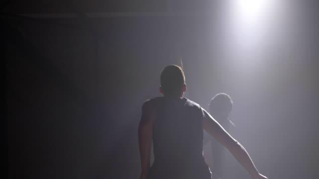 Zwei-Basketball-Spieler-Schatten-spielen-eins-zu-eins-drinnen-im-Zimmer-mit-Rauch-und-Flutlicht