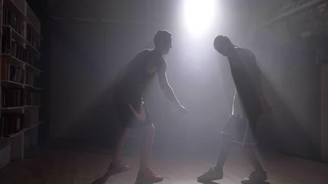Spieler-die-versuchen-den-Ball-von-einem-anderen-Spieler-im-Raum-mit-Rauch-und-Flutlicht-nehmen