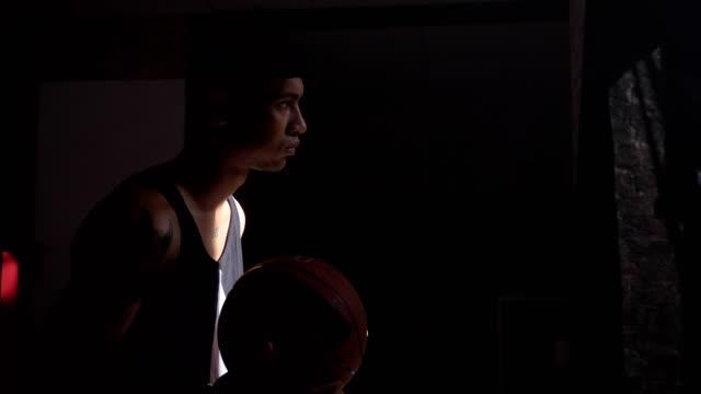 Jugador-de-baloncesto-africano-sentado-y-jugando-con-la-pelota-esperando-para-ir-al-patio-de-championnat