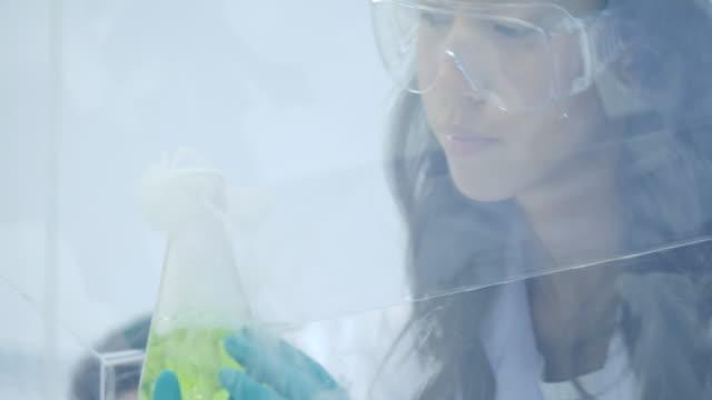 Investigadores-médicos-femeninos-ponen-hielo-seco-en-un-vaso-de-vidrio