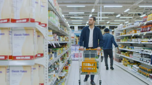 At-the-Supermarket:-Handsome-Man-Browses-Through-Shelf-with-Canned-Goods-Looks-at-Tin-Can-but-Decided-not-to-Buy-it-He-Proceeds-Walking-with-Shopping-Cart-Through-Different-Sections-of-the-Store-