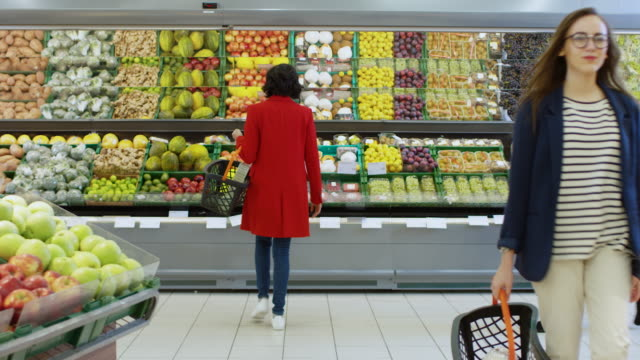 At-the-Supermarket:-Woman-Chooses-Organic-Fruits-in-the-Fresh-Produce-Section-of-the-Store-She-Picks-Up-Cantaloupe-and-Puts-them-into-Her-Shopping-Basket-Back-View-Shot-