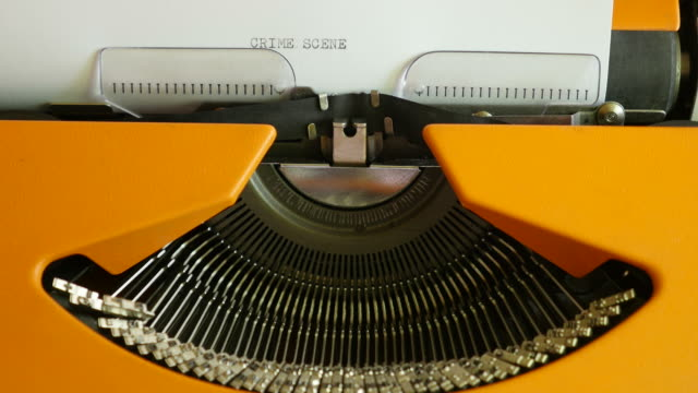 High-angle-shot-of-a-person-writing-CRIME-SCENE-on-an-old-typewriter-with-sound
