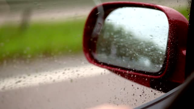 close-up-drops-of-water-on-side-window-of-car-while-driving-From-strong-wind-droplets-flow-not-down-the-glass-but-upwards-through-window-you-can-see-side-rearview-mirror
