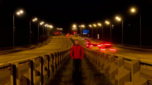 Ein-Mann-steht-auf-der-Autobahn-Autobahn-Verkehr-verschwommen-Autos-bei-Nacht-Zeitraffer-Autos-bewegen-unterwegs-auf-Brücke-Abend-Zeitraffer-4K-UHD