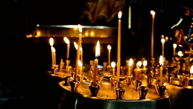 Mujer-enciende-una-vela-de-cera-en-un-incensario-en-un-antiguo-templo-católico-ortodoxo