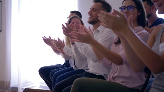 Grupo-empresarial-alegre-aplaudir-altavoz-después-de-la-presentación-en-el-primer-seminario-de-formación