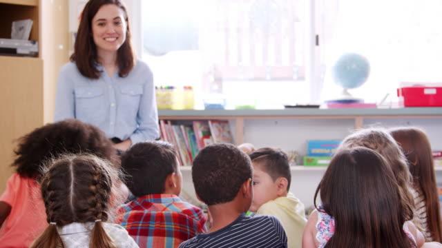 La-escuela-primaria-los-niños-levantan-las-manos-al-profesor-en-clase