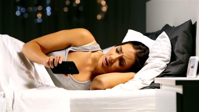 Mujer-nerviosa-esperando-un-mensaje-telefónico-en-la-noche