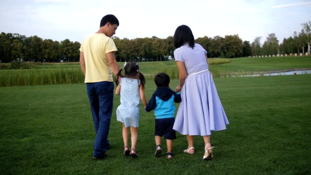 Asian-family-holding-hands-and-walking-outdoors