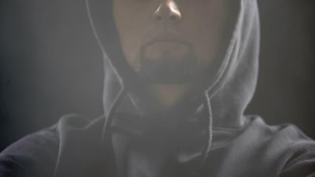 Gángster-peligroso-sentado-en-la-oscura-habitación-llena-de-humo-y-planificación-crimen-closeup